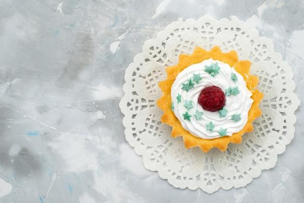 上のクローズアップビューグレーのデスクの甘いクリームにクリームとラズベリーの小さなおいしいケーキ