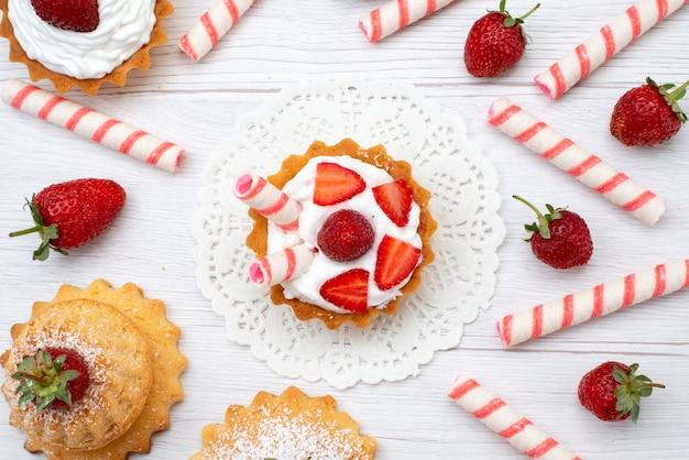 Top vista ravvicinata di piccole torte gustose con crema e fragole a fette caramelle su bianco