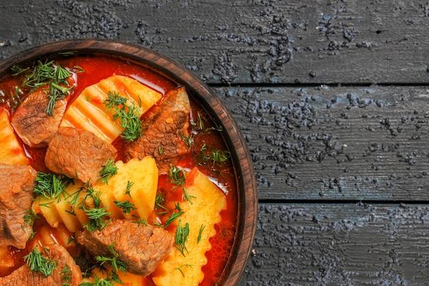Zuppa di carne vista ravvicinata superiore con patate e verdure su salsa di pasto piatto di carne scrivania scura