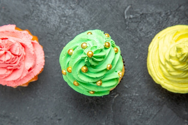Top close view mini colorful cupcakes on dark background