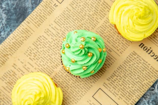 Mini cupcakes con vista dall'alto sul giornale su sfondo scuro
