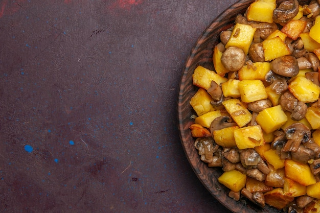 Vista dall'alto ravvicinata funghi e patate patate fritte e funghi in una ciotola su uno sfondo scuro