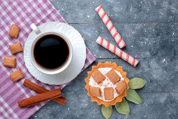 Вид сверху крупным планом на чашку горячего и крепкого кофе вместе с пирожными и корицей на сером, кофейном сладком напитке