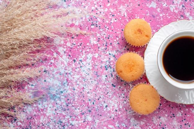 분홍색 표면에 작은 케이크와 함께 차 한잔의 상위 뷰 닫기