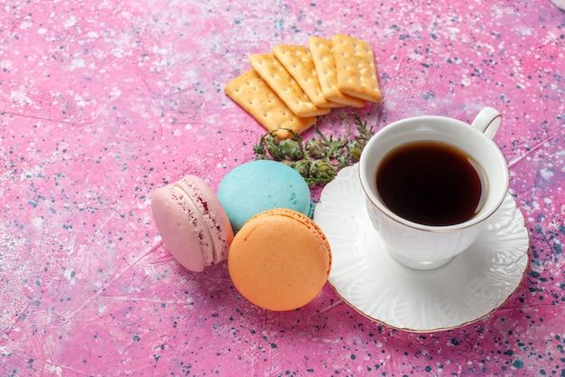 Вид сверху на чашку чая с вкусными французскими макаронами на розовой стене