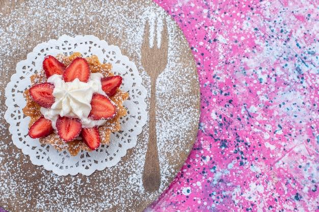 明るい紫色のケーキビスケットの甘い焼き色にクリームとスライスした赤いイチゴとおいしいケーキの上面拡大