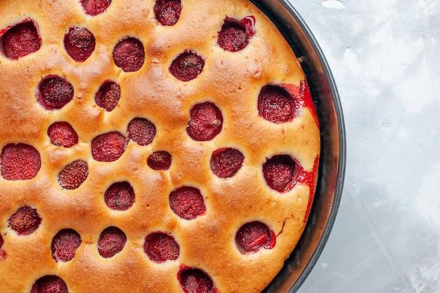 明るい白い机の上に鍋で新鮮な赤いイチゴで焼いたおいしいストロベリーケーキ、ケーキビスケットフルーツ甘い生地焼きの上面拡大図