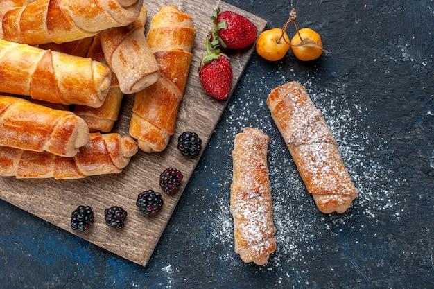 Вид сверху на вкусные сладкие браслеты с начинкой, запеченные с фруктами, на темном сладком десерте