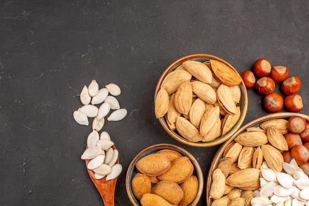 暗い表面の鉢の中のさまざまなナッツの新鮮なナッツの上面拡大図