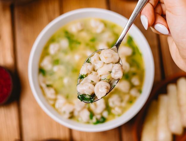乾燥ハーブとスパイスを添えたドゥシュバラ餃子スープの上部を閉じるビュー