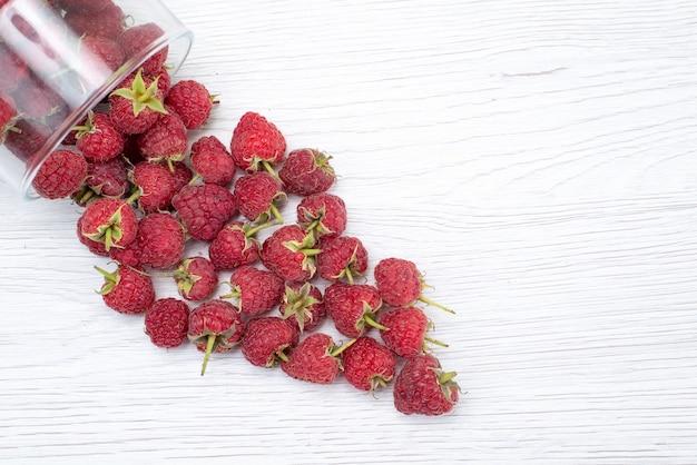 Вид сверху свежей красной малины внутри и снаружи миски на свету, ягодные свежие цветные фото