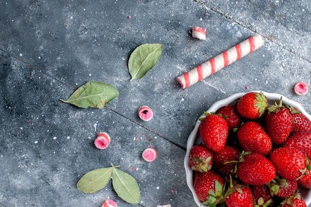 灰色のスティックキャンディー、フルーツベリーフレッシュキャンディーまろやかな甘いと一緒にプレート内の新鮮な赤いイチゴの上面拡大図