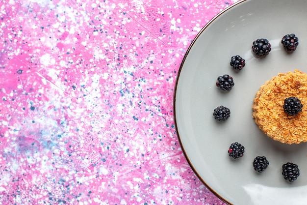Вид сверху крупным планом на маленький торт с ягодами на розовой поверхности