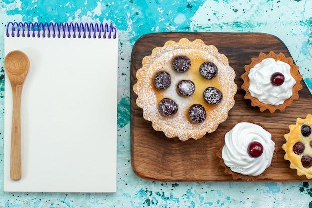Вид сверху на маленькие пирожные с фруктами и кремом алогн с блокнотом на светло-голубом цвете сладкого сахарного торта