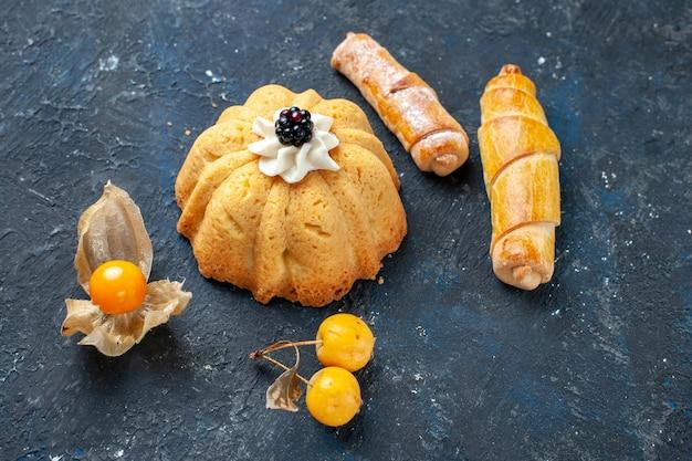 Вид сверху на маленький вкусный пирог со сладкими банхле на темном столе