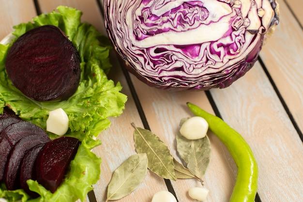 Вид сверху крупным планом на фиолетовую свеклу с фиолетовой капустой, зеленым салатом и чесноком на деревянном столе
