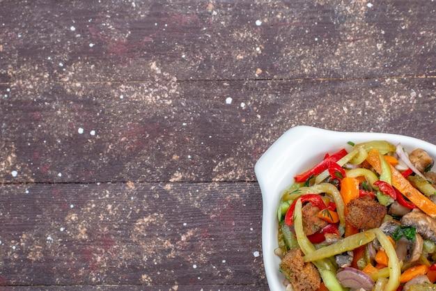 茶色のテーブルのプレートの内側に調理された野菜とスライスした肉料理の上面拡大図