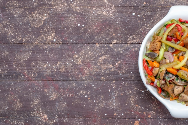 茶色のプレートの内側に調理された野菜とスライスした肉料理の上面拡大図