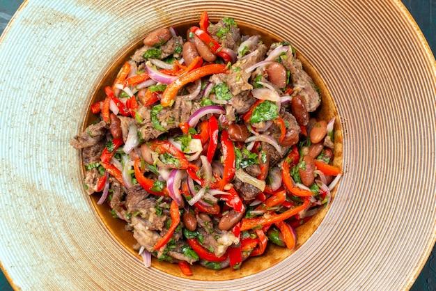 暗闇の中でプレートの中に肉が入ったスライス野菜サラダの上面拡大図