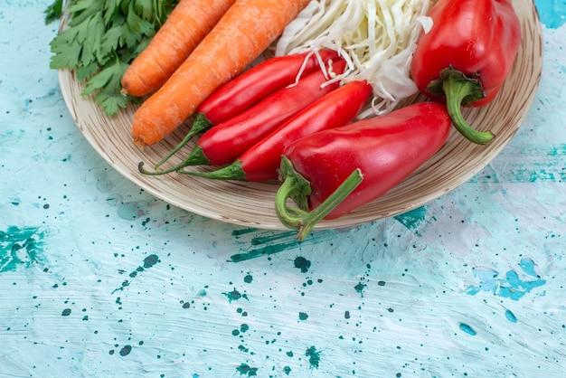 Вид сверху крупным планом на овощную композицию, капусту, морковь, зелень и красный острый перец на ярко-синем столе