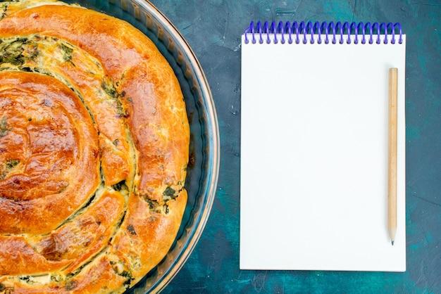 Pasticceria vista ravvicinata dall'alto con verdure al forno insieme al blocco note su sfondo blu.