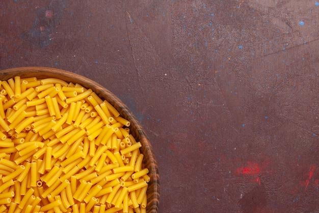Вид сверху крупным планом сырые итальянские макароны, мало сформированные на темном пространстве