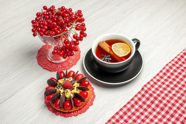 Сверху крупным планом красная смородина в хрустальном бокале на красной овальной кружевной салфетке и чашка чая с лимоном и корицей и красно-белая клетчатая скатерть на белом деревянном столе