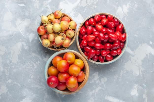 Красный кизил со сливой и вишней на белом столе крупным планом, свежий фруктовый сок, витамин