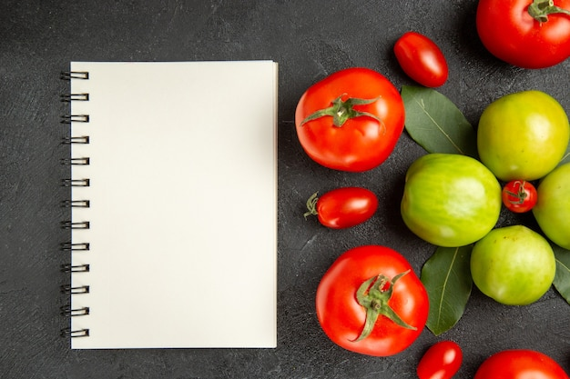 Top close view red and green tomatoes bay leaves around a cherry tomato and a notebook on dark ground