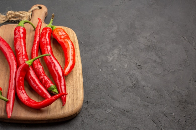 Top close view red hot peppers on a chopping board at the left side of the black table with copy space