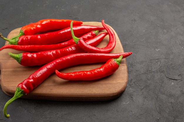 Top close view red hot peppers on a horizontal chopping board on the black table with copy space