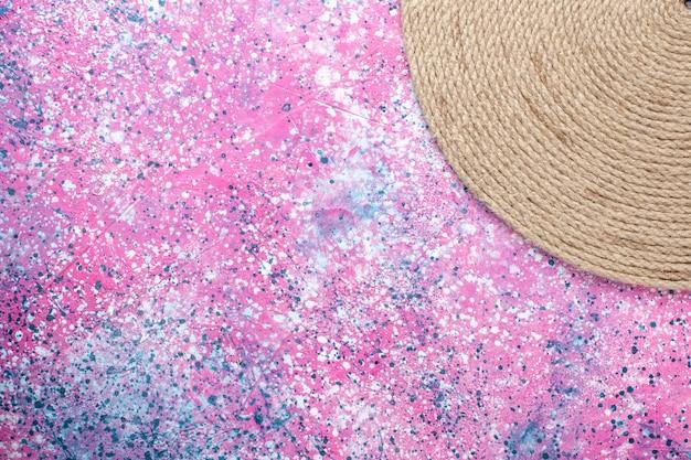 Top vista ravvicinata corde formate rotonde su sfondo rosa. sfondo di foto a colori di corda.