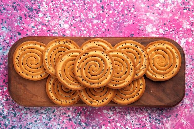 Vista ravvicinata superiore biscotti dolci rotondi allineati sulla scrivania rosa.