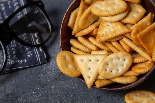 Вид сверху соленые вкусные крекеры внутри коричневой тарелки с солнцезащитными очками на сером столе фото закуски хрустящего крекера