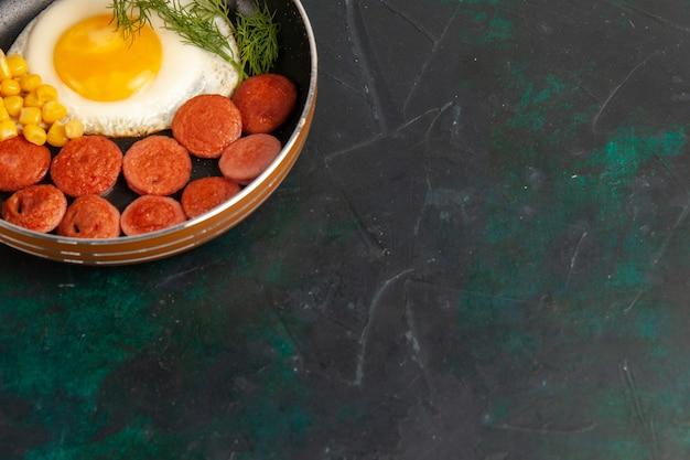 暗い表面の鍋の中にスライスしたソーセージと緑のスクランブルエッグを上から見る