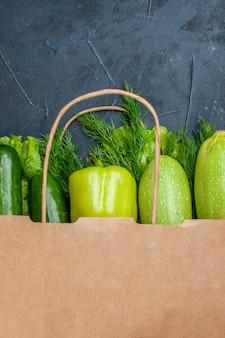 Vista ravvicinata borsa della spesa cetrioli peperone zucchine lattuga aneto sul tavolo nero