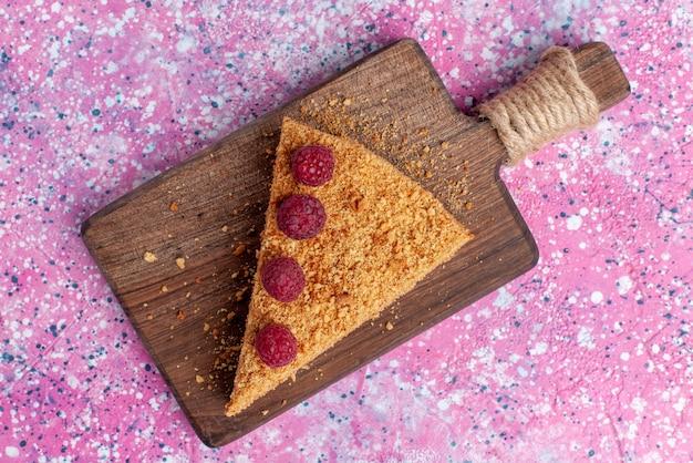 Top vista ravvicinata fetta di torta al forno e dolce con lamponi sulla scrivania rosa brillante cuocere torta dolce torta frutta