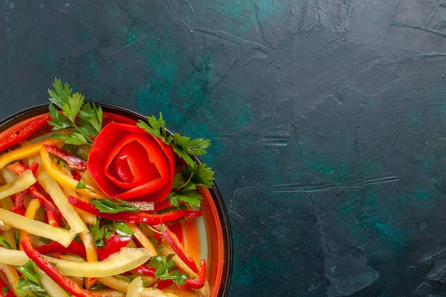 紺色の表面のプレート内のスライスしたピーマンの異なる色の野菜サラダを上から見る