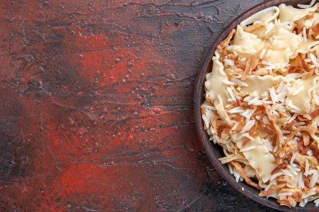 トップクローズビュースライスした調理済み生地とご飯を暗い表面の生地パスタ料理の食事に