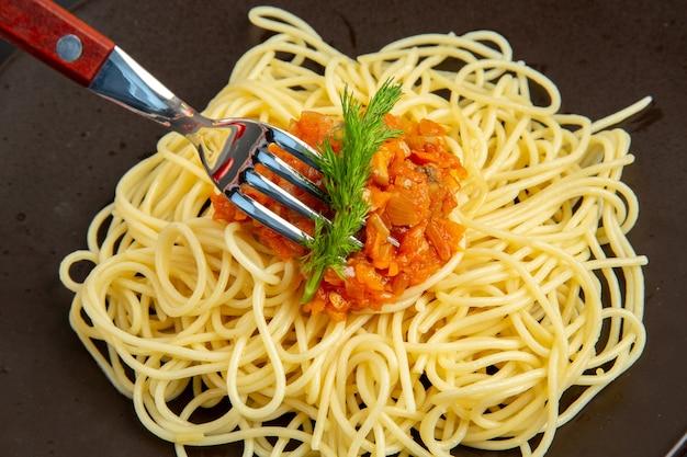 Spaghetti vista ravvicinata dall'alto con salsa sulla forchetta del piatto sul tavolo nero