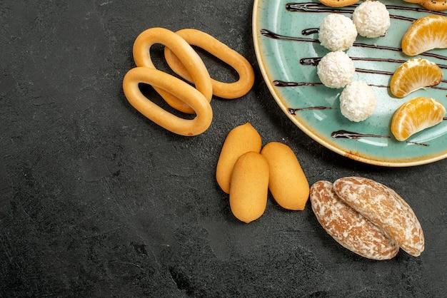 灰色のテーブルビスケットの甘いクッキーにキャンディーとトップクローズビューの甘いビスケット