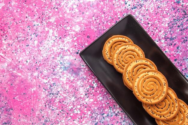 Vista ravvicinata dall'alto biscotti dolci deliziosi piccoli biscotti all'interno del modulo nero sulla scrivania rosa chiaro.