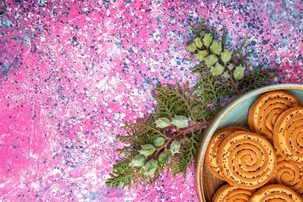 Сверху крупным планом сладкое печенье вкусное маленькое печенье на светло-розовом столе.