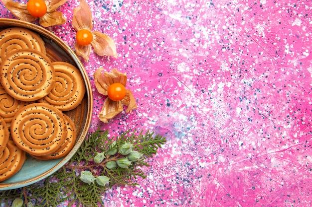 Vista ravvicinata dall'alto biscotti dolci deliziosi piccoli biscotti con fisici sulla scrivania rosa chiaro.
