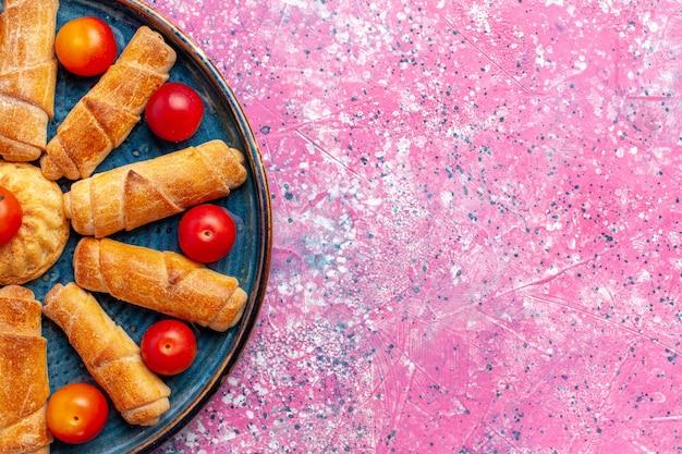 Сверху крупным планом сладкие вкусные рогалики запеченная выпечка внутри подноса со сливами на розовом столе выпечка кондитерского торта бисквитное печенье сладкий сахар