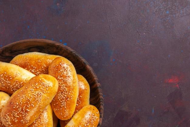 Сладкие пирожки сверху крупным планом, вкусное запеченное тесто для чая на темном пространстве