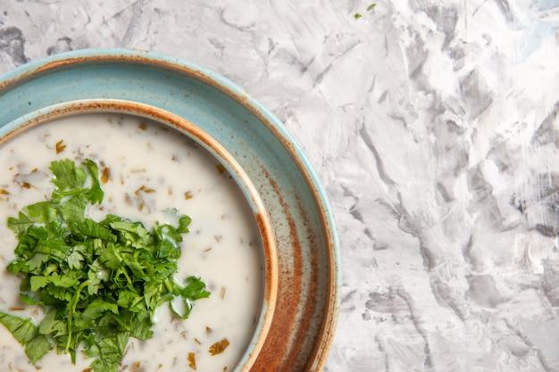 Vista dall'alto ravvicinata gustosa zuppa di yogurt dovga con verdure su pasto bianco di zuppa di latte da tavola