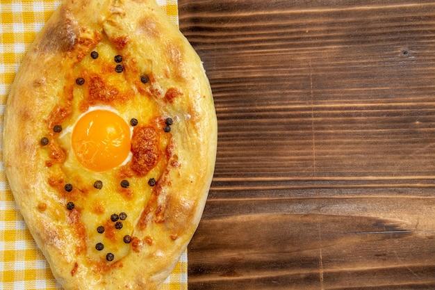 Top vista ravvicinata gustoso pane all'uovo appena sfornato sul tavolo in legno pasto pane panino colazione uovo