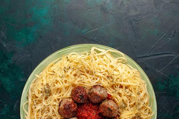 Vista ravvicinata gustosa pasta italiana con polpette sulla superficie blu scuro