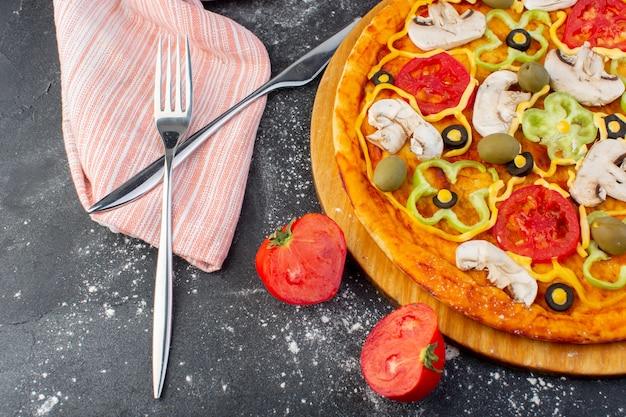 暗い机の上で新鮮なトマトと赤いトマトグリーンオリーブキノコとおいしいキノコのピザを閉じるトップビューピザ生地イタリア料理